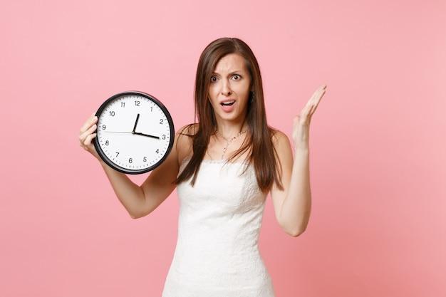 Раздраженная женщина в белом платье раздвигает руку и держит круглый будильник