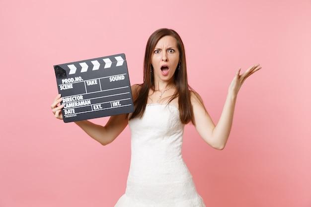 カチンコを作る古典的な黒い映画を持っている手を広げて誓う白いドレスを着たイライラした女性