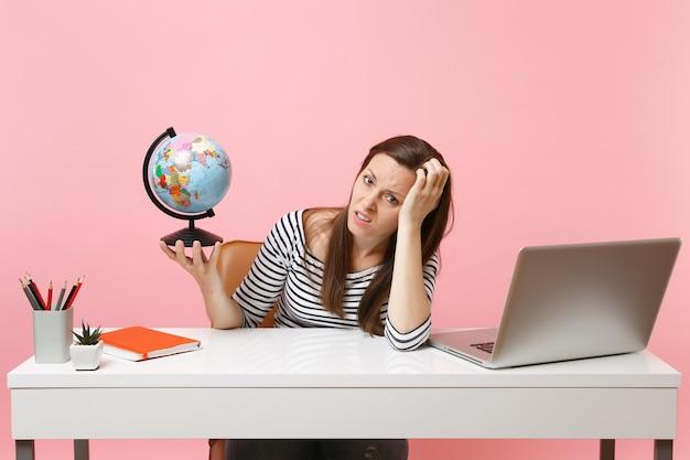 座っている間、休暇の計画に問題がある地球を持って手に寄りかかっているイライラした女性は、パステルピンクの背景に分離されたラップトップでオフィスで働いています。業績ビジネスキャリア。スペースをコピーします。