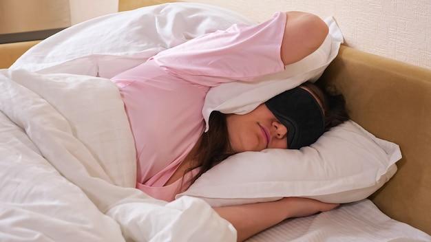 특별한 검은색 잠자는 마스크와 분홍색 잠옷을 입은 짜증난 여성은 소음이 나지 않도록 손과 큰 흰색 베개로 귀를 닫고 침대에 누워 있습니다.