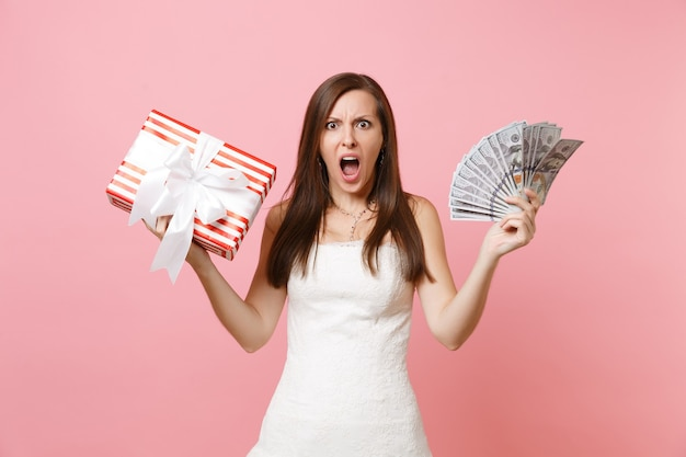 Donna irritata in abito bianco che urla tenendo in mano un sacco di dollari in contanti scatola rossa con regalo, regalo