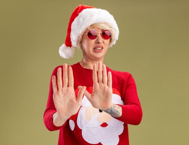 올리브 녹색 배경에 고립 거부 제스처를 하 고 카메라를보고 안경 크리스마스 모자와 산타 클로스 크리스마스 스웨터를 입고 염증 된 젊은 금발의 여자
