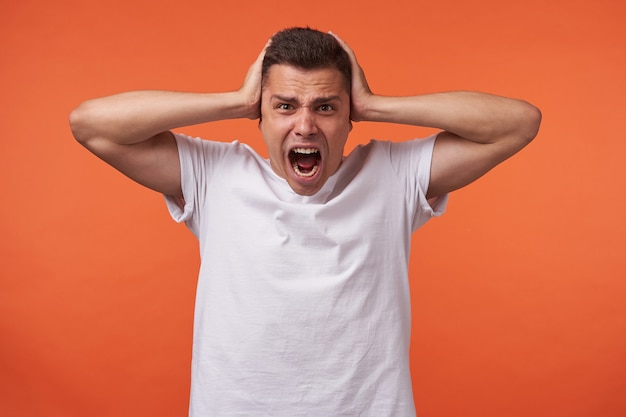 Irritated young brown-eyed short haired male covering his ears with raised palms and keeping mouth opened while screaming excitedly, isolated over orange background