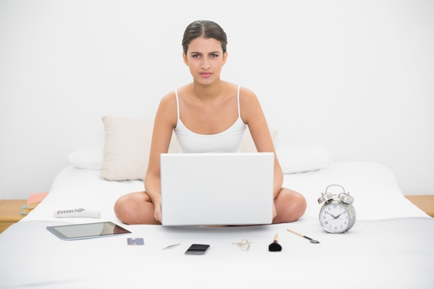 Irritated young brown haired model in white pajamas holding a laptop
