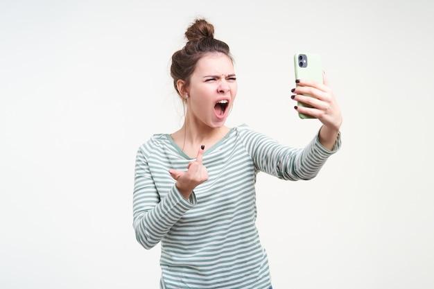 Giovane donna dai capelli castani irritata che aggrotta le sopracciglia mentre urla follemente e alza la mano con il gesto del cazzo durante la conversazione video, isolato sopra il muro bianco