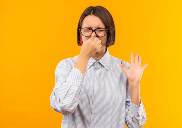 Раздраженная молодая девушка колл-центра в очках держит нос и показывает пустую руку с закрытыми глазами, изолированными на оранжевом
