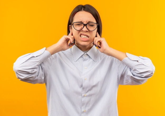 Irritated young call center girl wearing glasses putting fingers in ears with closed eyes isolated on orange