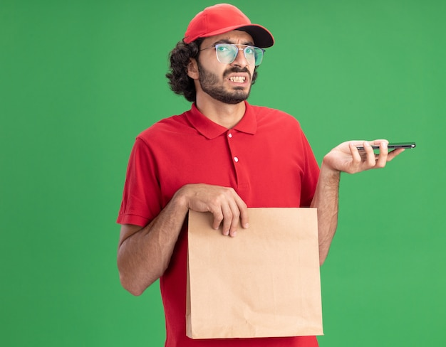 Irritated young caucasian delivery man in red uniform and cap wearing glasses holding paper package and mobile phone