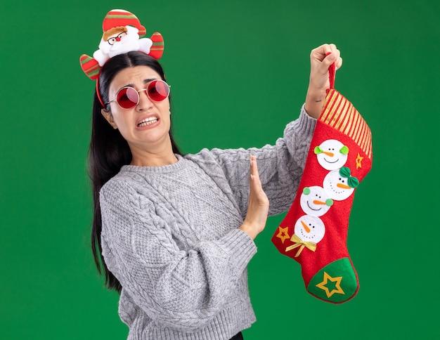 녹색 배경에 고립 거부 제스처를 하 고 카메라를보고 크리스마스 스타킹을 들고 안경 산타 클로스 머리 띠를 착용 초조 젊은 백인 여자