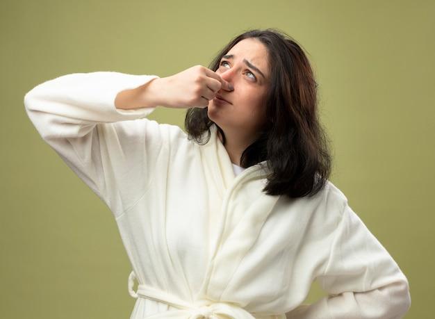 Раздраженная молодая кавказская больная девушка в халате, держащая нос, держа руку на талии, глядя вверх изолирована на оливково-зеленом фоне