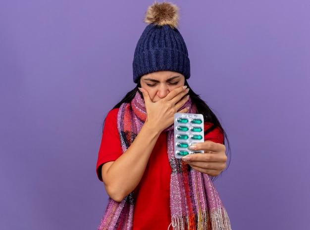 Irritato giovane indoeuropea ragazza malata che indossa cappello invernale e sciarpa che allunga il pacchetto di capsule verso la telecamera tenendo la mano sulla bocca con gli occhi chiusi isolato su sfondo viola con spazio di copia