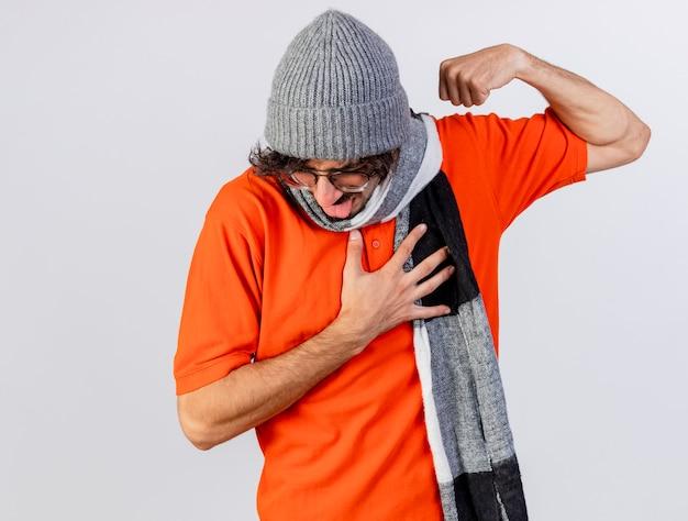 眼鏡の冬の帽子とスカーフを身に着けているイライラした若い白人の病気の人は、コピースペースで白い背景に分離された舌を示す胸に手を保ちながら強いジェスチャーをしています