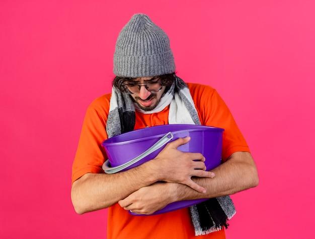 Irritato giovane indoeuropeo uomo malato con gli occhiali inverno cappello e sciarpa tenendo il secchio di plastica con nausea guardando in basso isolato su sfondo cremisi