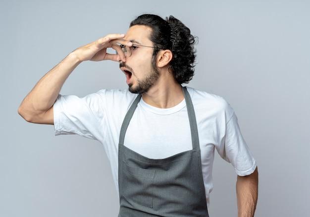 眼鏡と波状の髪のバンドを身に着けているイライラした若い白人男性の理髪師は、側面を見て、白い背景で隔離の鼻を保持している