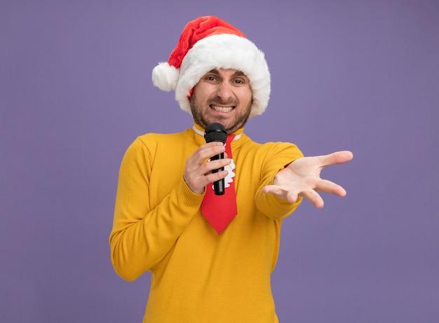 Раздраженный молодой кавказец в рождественской шляпе и галстуке держит микрофон, глядя в камеру, протягивая руку к камере, изолированной на фиолетовом фоне