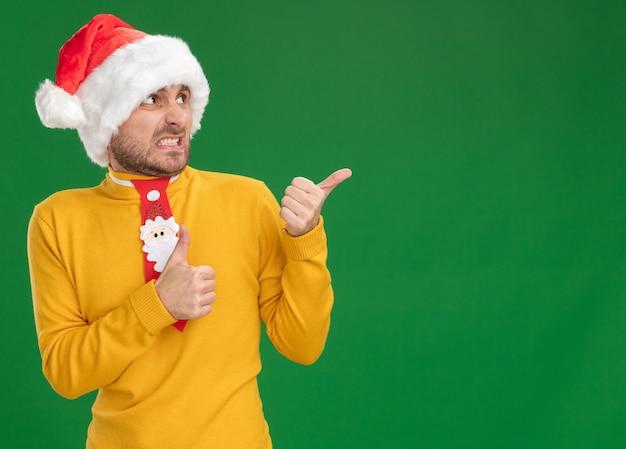 크리스마스 모자와 넥타이를 착용하고 녹색 배경에 고립 엄지 손가락을 보여주는 측면에서 가리키는 짜증이 젊은 백인 남자