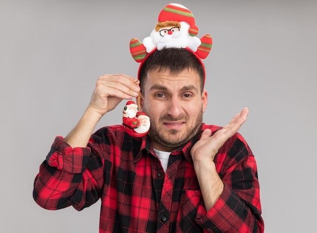 サンタクロースのヘッドバンドを身に着けているイライラした若い白人男性が白い背景で隔離の空の手を示す頭の近くにサンタクロースのクリスマス飾りを保持しているカメラを見て
