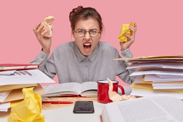 Irritated young caucasian worker keeps crag of papers, opens mouth widely, frowns face, wears shirt and spectacles, reads textbook, analyzes documentation