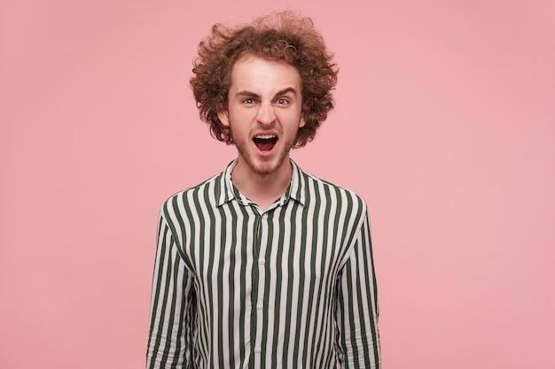 넓은 입으로 화가 나서 외치는 수염을 가진 젊은 곱슬 빨간 머리 남자가 카메라를 보면서 열리고, 손으로 분홍색 벽 위에 포즈를 취합니다.