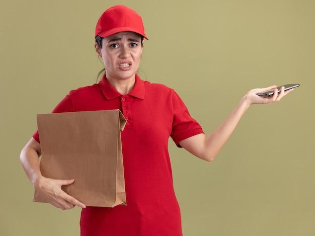 Giovane donna delle consegne irritata in uniforme e cappuccio che tiene in mano un pacchetto di carta e un telefono cellulare isolato su una parete verde oliva