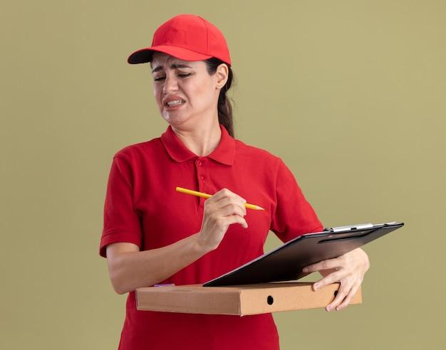 Irritata giovane donna delle consegne in uniforme e cappello che tiene il pacchetto di pizza negli appunti e matita guardando in basso