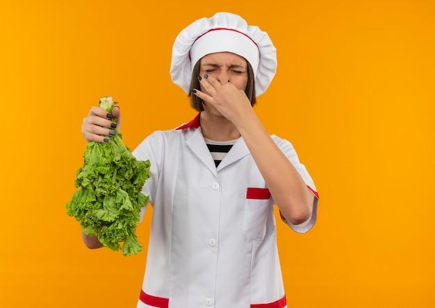 オレンジ色に分離された目を閉じてレタスと彼女の鼻を保持しているシェフの制服を着たイライラした若い女性料理人