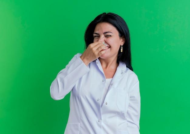 Irritato giovane medico femminile che indossa abito medico tenendo il naso isolato sulla parete verde con lo spazio della copia