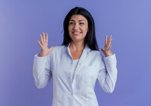 医療ローブを着て、横を見て手を空中に保つイライラした若い女性医師