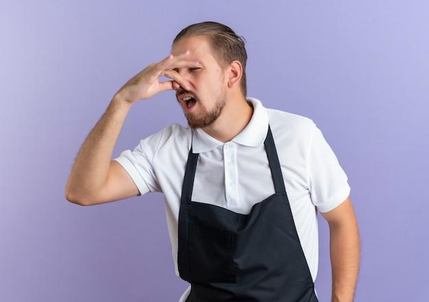 紫色で隔離された目を閉じて彼の鼻を保持している制服を着てイライラした若いハンサムな床屋
