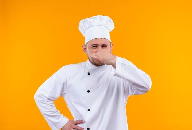 孤立したオレンジ色の壁の腰に別の手で鼻を保持しているシェフの制服を着たイライラした若いハンサムな料理人