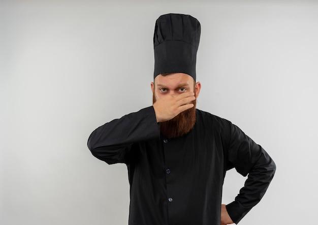 コピー スペースで白い壁に分離された腰に手で鼻を保持しているシェフの制服を着たイライラした若いハンサムな料理人