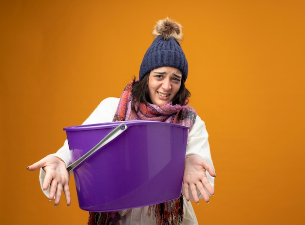 Раздраженная молодая больная женщина в зимней шапке и шарфе, испытывающая тошноту, протягивает пластиковое ведро вперед, глядя вперед, изолированное на оранжевой стене