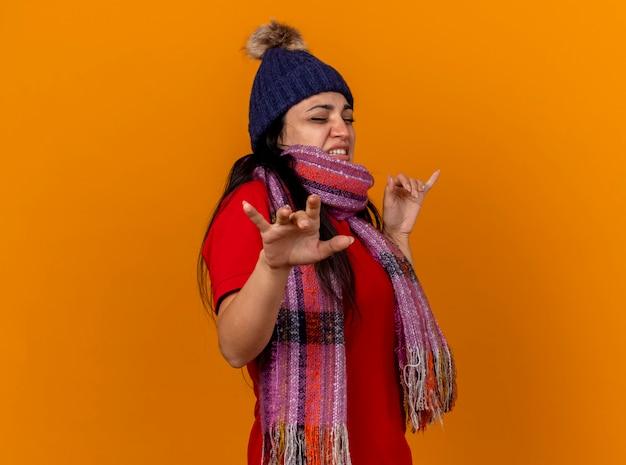 Раздраженная молодая больная женщина в зимней шапке и шарфе стоит в профиль, держа руки в воздухе с закрытыми глазами, изолированными на оранжевой стене