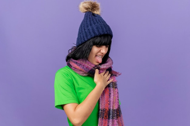 Irritated young ill woman wearing winter hat and scarf keeping hand on chest showing tongue with closed eyes isolated on purple wall with copy space