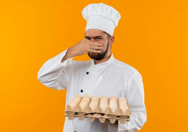 Irritated young male cook in chef uniform holding carton of eggs and his nose isolated on orange wall