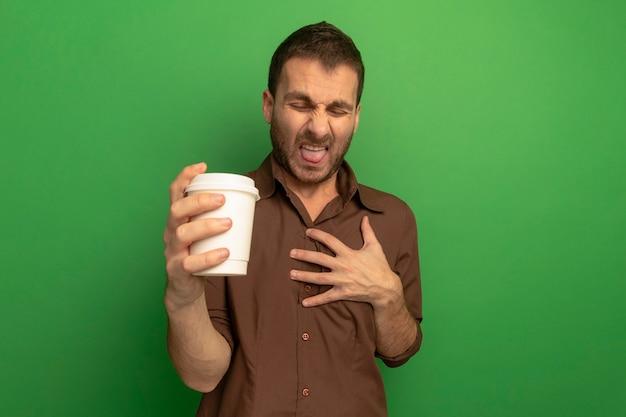 緑の壁に隔離された目を閉じて舌を示す胸に手を保持してプラスチック製のコーヒーカップを保持しているイライラした若い男