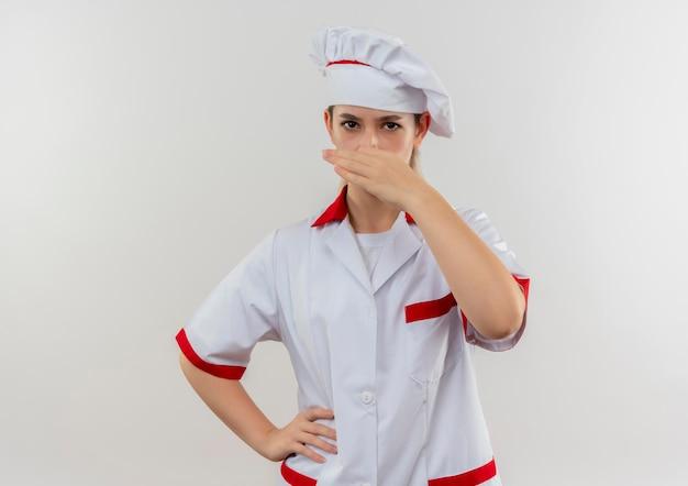腰に手を置き、白い壁に分離された鼻を保持しているシェフの制服を着たイライラした若いきれいな料理人