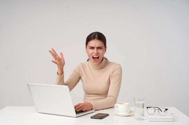 Irritata giovane donna dai capelli scuri che alza eccitata la mano mentre guarda con rabbia, aggrottando la fronte mentre urla con la bocca spalancata, isolata sopra il muro bianco