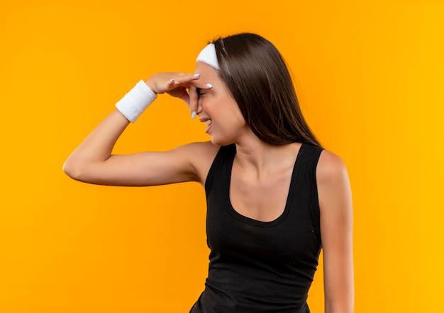 Giovane ragazza piuttosto sportiva irritata che indossa fascia e cinturino che tiene il naso isolato sul muro arancione orange