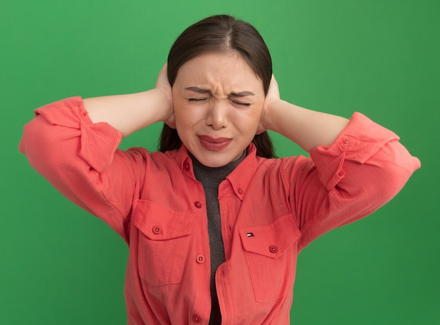 Giovane donna graziosa irritata che copre le orecchie con le mani con gli occhi chiusi isolati sul muro verde green
