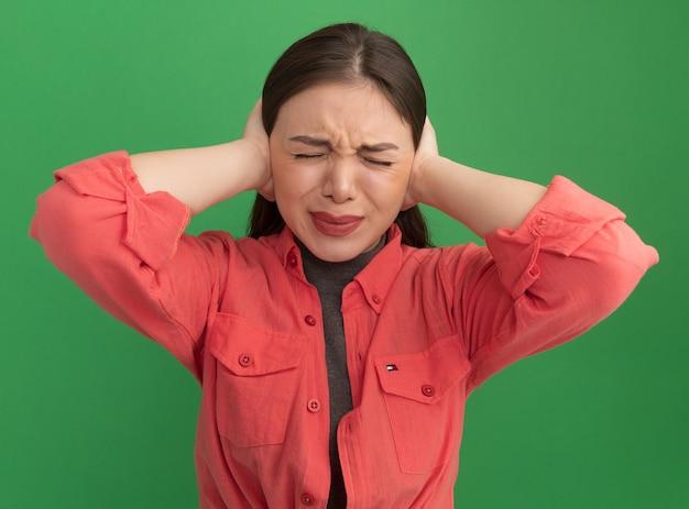 緑の壁に隔離された目を閉じて手で耳を覆うイライラした若いきれいな女性