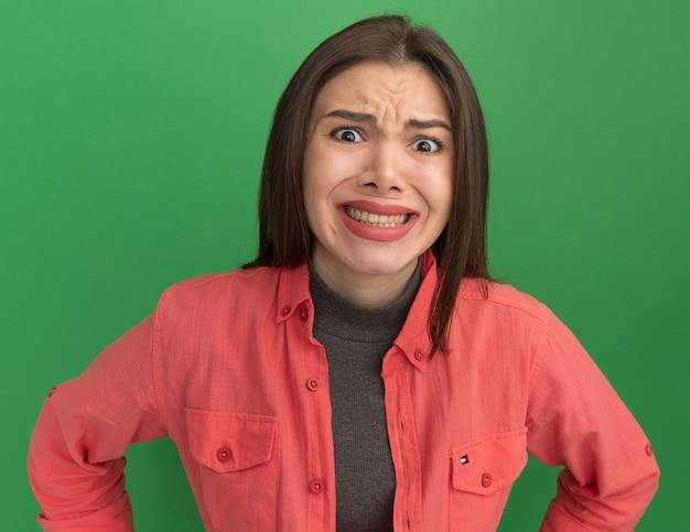Giovane donna graziosa irritata che tiene le mani sulla vita isolata sulla parete verde