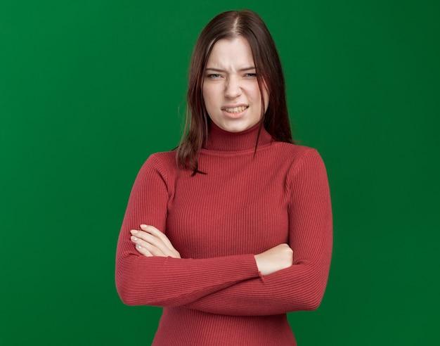 Раздраженная молодая красивая женщина, стоящая в закрытой позе, смотрящая вперед, изолирована на зеленой стене с копией пространства