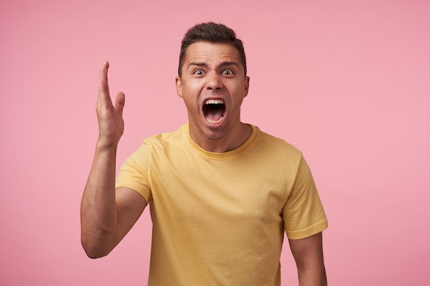 Irritated young short haired brunette man with short haircut screaming crossly with wide mouth opened and raising emotionally palm while posing over pink background