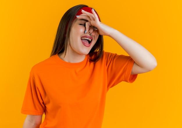 Giovane donna sportiva irritata che indossa fascia e braccialetti tenendo il naso con gli occhi chiusi