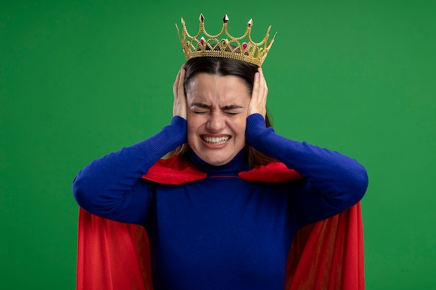 Ragazza irritata del supereroe giovane che indossa la corona che mette le mani sulle orecchie isolate sul verde