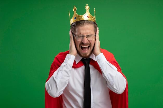 緑の背景で隔離の耳に手を置いて王冠とネクタイを身に着けているイライラした若いスーパーヒーローの男