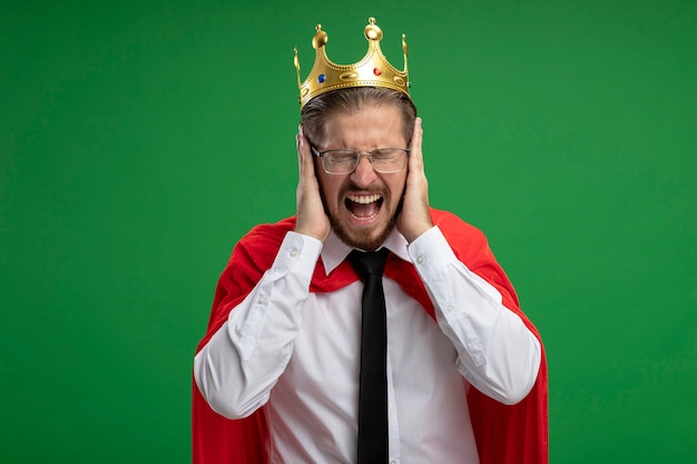 Irritated young superhero guy wearing crown and tie putting hands on ears isolated on green background