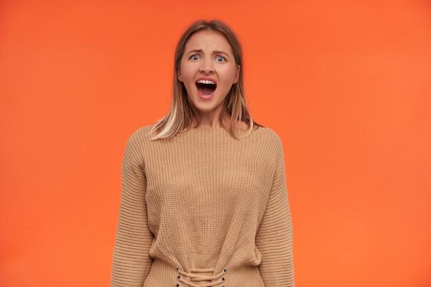 Irritata giovane donna dai capelli bianchi con un taglio di capelli corto che tiene la bocca spalancata mentre guarda di fronte in modo incrociato, in posa sul muro arancione con le mani in basso