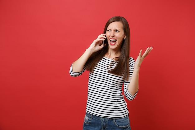 화가 난 젊은 여성은 밝은 붉은 벽 배경에서 격리된 대화를 하며 휴대전화로 손을 벌리고 비명을 질렀다. 사람들은 진심 어린 감정, 라이프 스타일 개념입니다. 복사 공간을 비웃습니다.